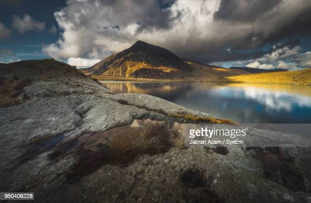 scenic view of lake by mountains against sky - snowdonia stock photos and pictures