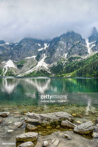 scenic view of lake by mountains against sky - zakopane stock pictures, royalty-free photos & images