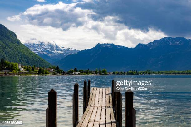 scenic view of lake by mountains against sky,avenue de chillon,veytaux,switzerland - montreux stock pictures, royalty-free photos & images