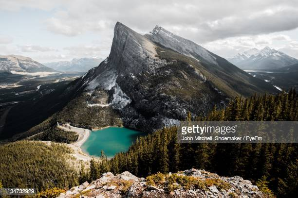 scenic view of lake by mountains during winter - banff stock photos and pictures
