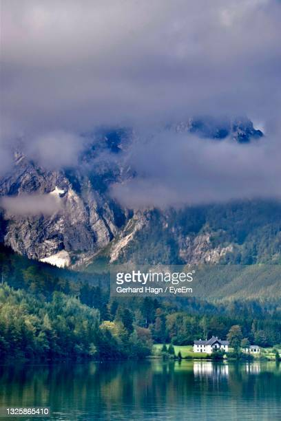 scenic view of lake by mountains in fog - gerhard hagn stock-fotos und bilder