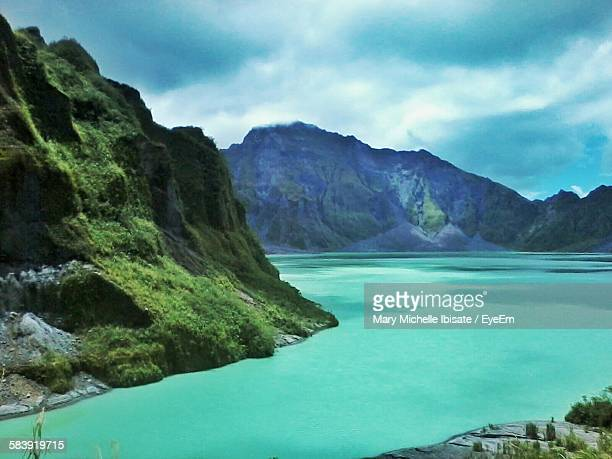 scenic view of lake by mt pinatubo against cloudy sky - mt pinatubo stock photos and pictures