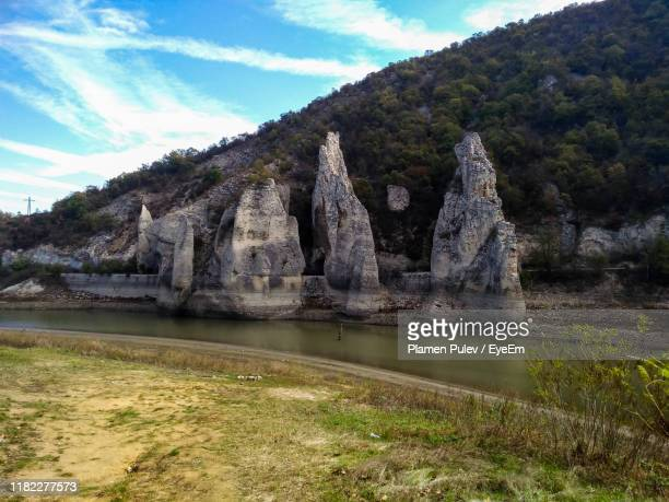 scenic view of lake by rock formation against sky - pulev stock photos and pictures