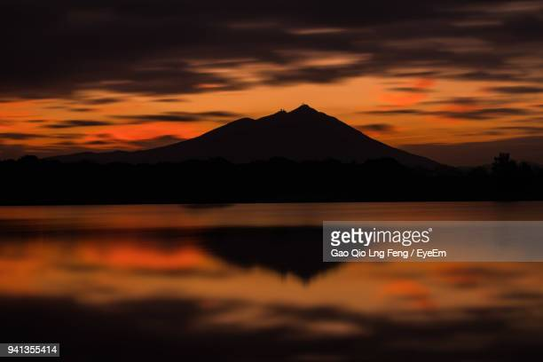 scenic view of lake by silhouette mountains against orange sky - 茨城県 ストックフォトと画像