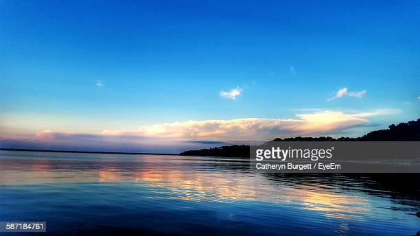 scenic view of lake by silhouette trees against blue sky - waco stockfoto's en -beelden