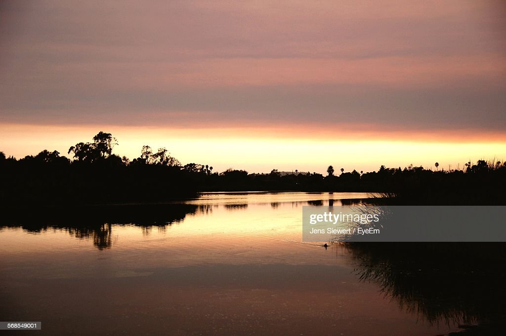 Scenic View Of Lake By Silhouette Trees Against Cloudy Sky : Stock Photo