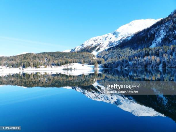 scenic view of lake by snowcapped mountains against clear blue sky - davos stock pictures, royalty-free photos & images