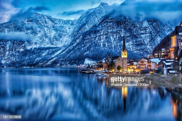 scenic view of lake by snowcapped mountains against sky at night,hallstatt,austria - hallstatt fotografías e imágenes de stock