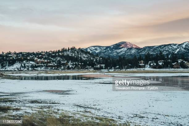 scenic view of lake by snowcapped mountains against sky during sunset - big bear lake stock photos and pictures