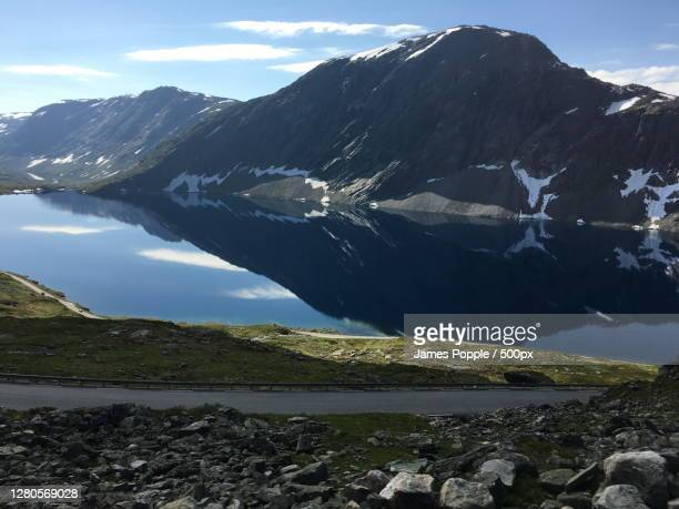 scenic view of lake by snowcapped mountains against sky, nibbevegen, geiranger, norway - james popple foto e immagini stock