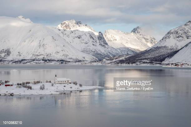 scenic view of lake by snowcapped mountains against sky - marek stefunko stockfoto's en -beelden