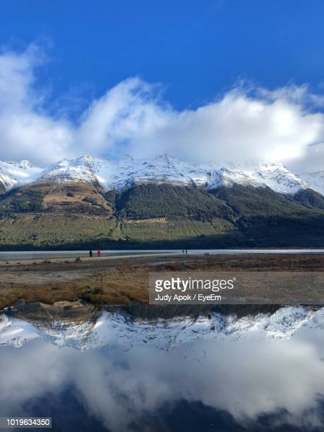 scenic view of lake by snowcapped mountains against sky - judy winter stock-fotos und bilder