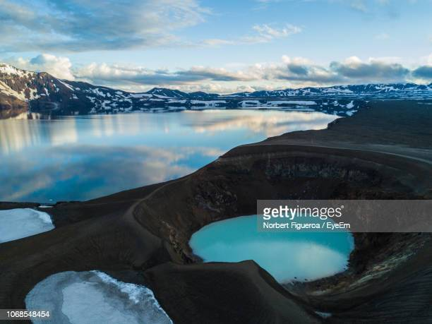 scenic view of lake by snowcapped mountains against sky - iceland stock pictures, royalty-free photos & images