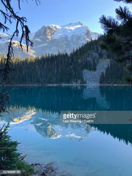scenic view of lake by snowcapped mountains against sky - lisa pemberton stock pictures, royalty-free photos & images
