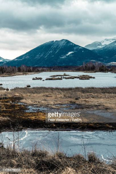 scenic view of lake by snowcapped mountains against sky - weilacher stock-fotos und bilder