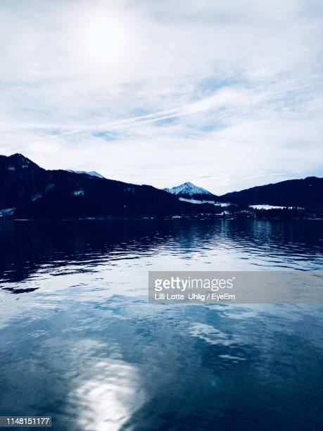 scenic view of lake by snowcapped mountains against sky - tegernsee photos et images de collection