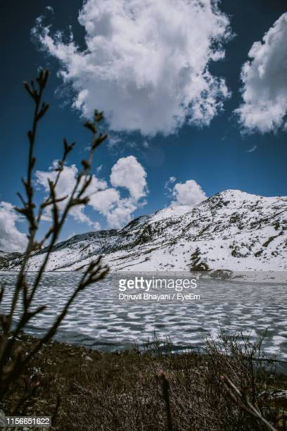 scenic view of lake by snowcapped mountains against sky - sikkim stock pictures, royalty-free photos & images