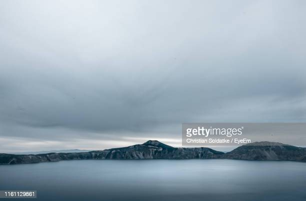 scenic view of lake by snowcapped mountains against sky - christian soldatke stock pictures, royalty-free photos & images