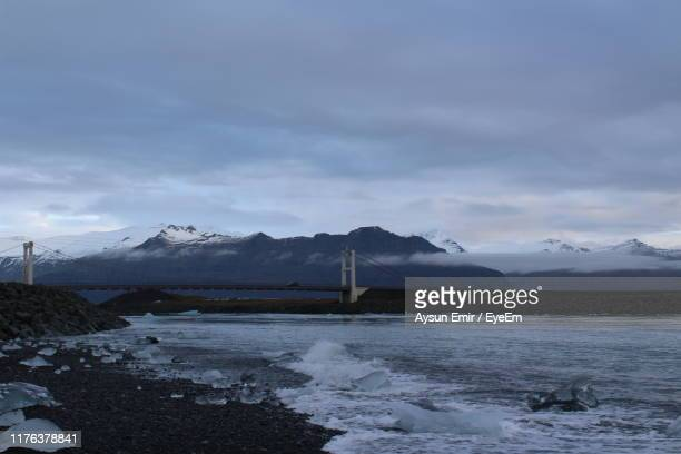 scenic view of lake by snowcapped mountains against sky - punalu'u_beach stock pictures, royalty-free photos & images