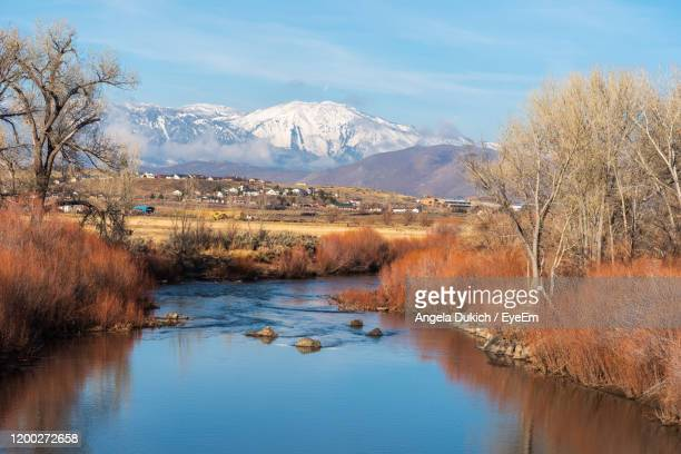 scenic view of lake by snowcapped mountains against sky - carson california stock pictures, royalty-free photos & images