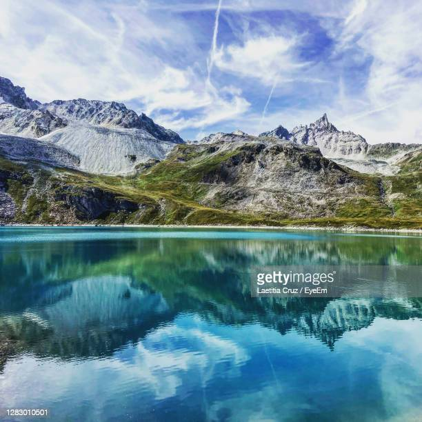 scenic view of lake by snowcapped mountains against sky - 氷河湖 ストックフォトと画像