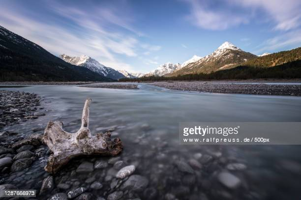 scenic view of lake by snowcapped mountains against sky - wasser stock pictures, royalty-free photos & images