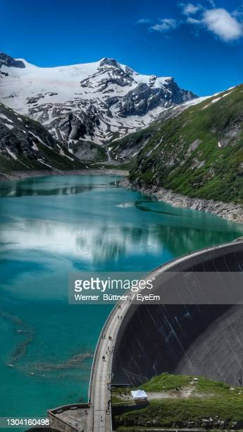 scenic view of lake by snowcapped mountains against sky - stausee stock-fotos und bilder