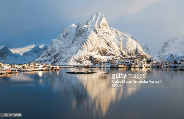 scenic view of lake by snowcapped mountains against sky,reine,norway - images stock pictures, royalty-free photos & images