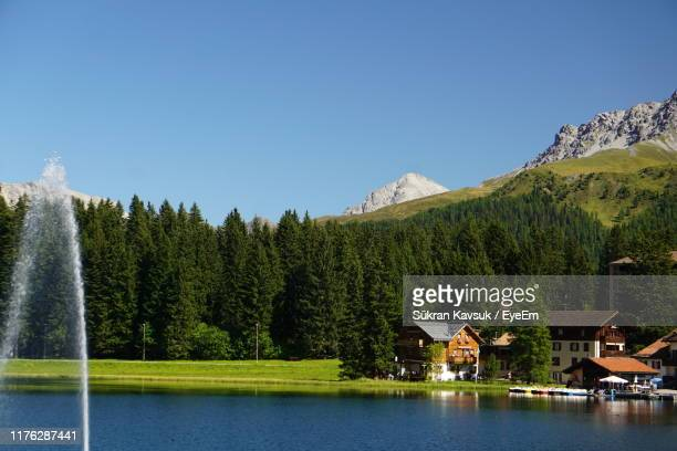 scenic view of lake by trees against clear sky - アロサ ストックフォトと画像
