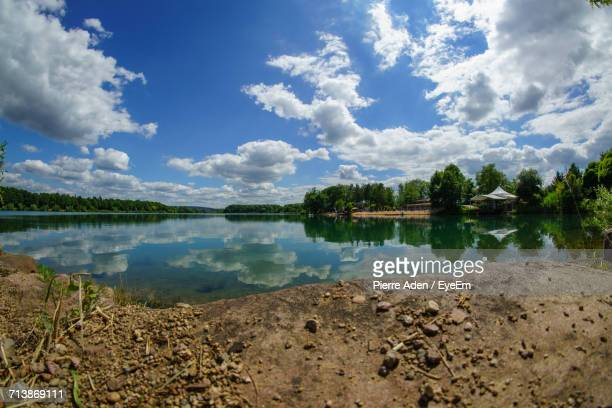 Scenic View Of Lake By Trees Against Cloudy Sky