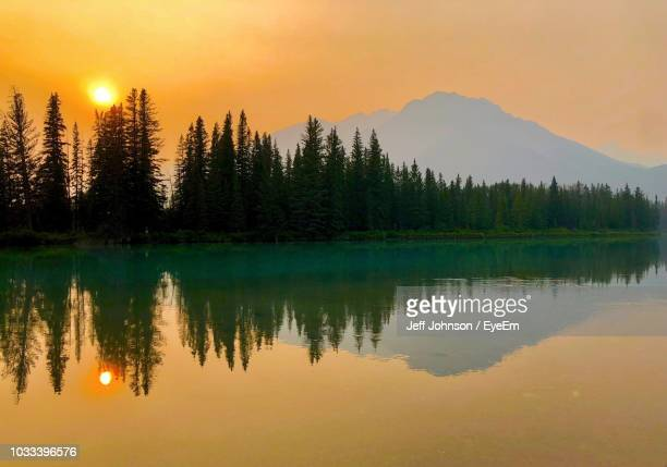 scenic view of lake by trees against orange sky - reflection lake stock photos and pictures