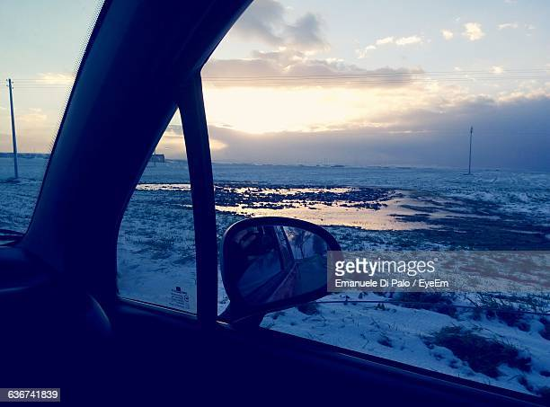scenic view of lake during winter seen through car window - spinazzola foto e immagini stock