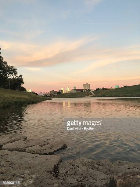 Scenic View Of Lake In City Against Cloudy Sky