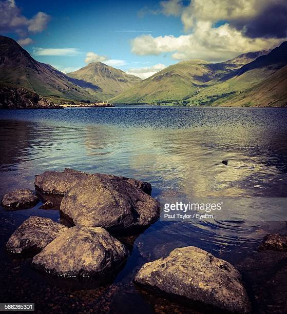 Scenic View Of Lake In Front Of Mountains Against Cloudy Sky