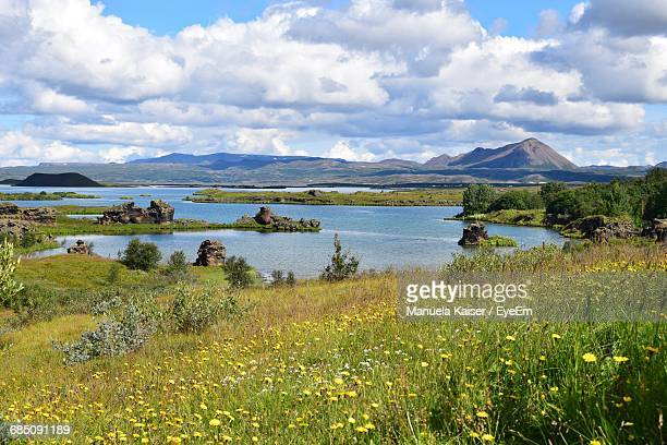 Scenic View Of Lake Myvatn By Mountains Against Cloudy Sky