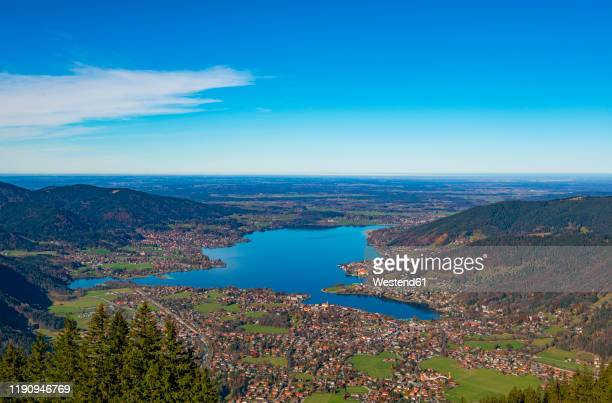 scenic view of lake tegernsee and wallberg mountains against blue sky during sunny day, bavaria, germany - tegernsee stock pictures, royalty-free photos & images
