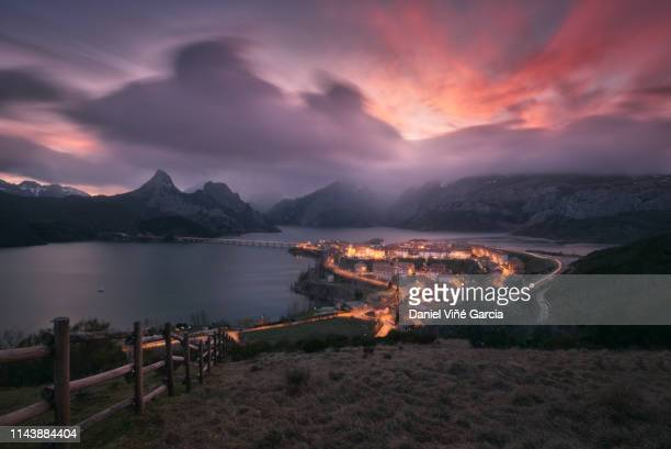 scenic view of lake, village and mountains against sky at sunset, riaño, castilla y leon, spain. - castilla leon fotografías e imágenes de stock