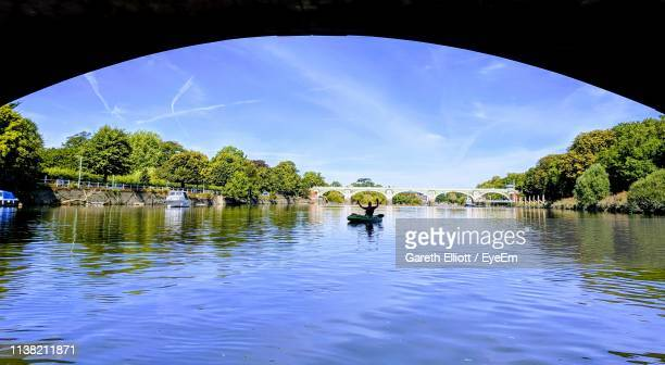scenic view of lake with man sitting on inflatable boat against sky - richmond upon thames stock pictures, royalty-free photos & images