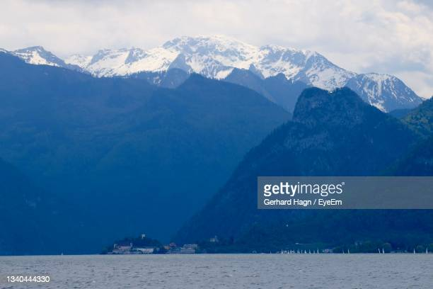 scenic view of lake with village and snowcapped mountains against sky - gerhard hagn stock-fotos und bilder
