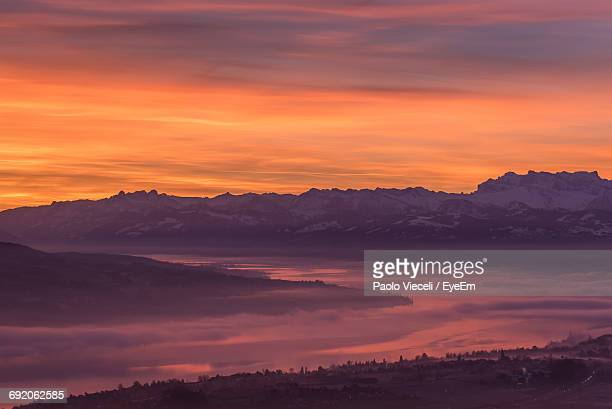 Scenic View Of Lake Zurich And Mountains Against Orange Sky