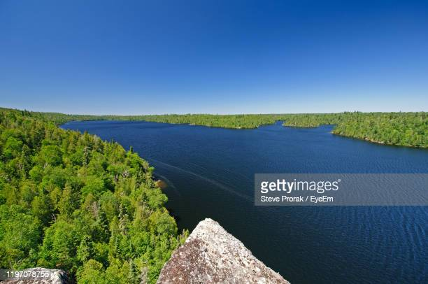 scenic view of land against clear blue sky - boundary waters canoe area stock pictures, royalty-free photos & images