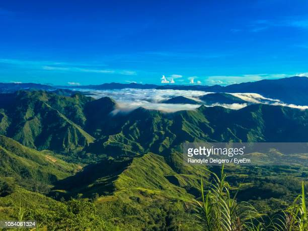 scenic view of landscape against blue sky - davao city stock photos and pictures