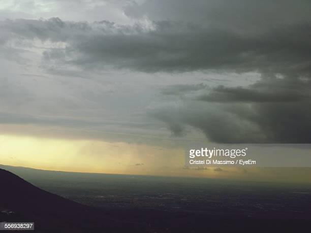 Scenic View Of Landscape Against Cloudy Sky At Dusk