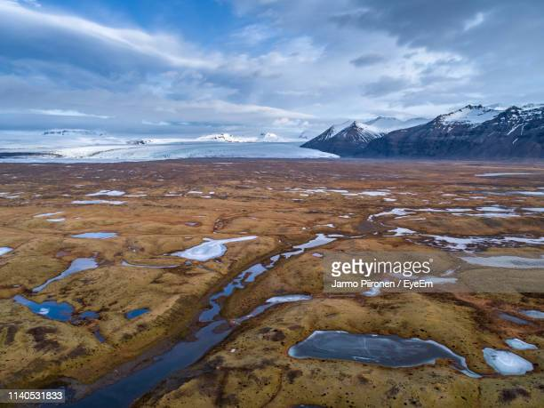 scenic view of landscape against cloudy sky during winter - tundra stock pictures, royalty-free photos & images