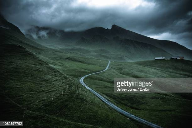 scenic view of landscape against cloudy sky - country road stock pictures, royalty-free photos & images