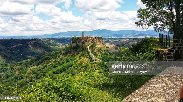 scenic view of landscape against cloudy sky - civita di bagnoregio foto e immagini stock