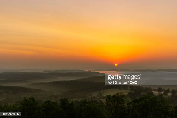 scenic view of landscape against orange sky - arkansas stock pictures, royalty-free photos & images
