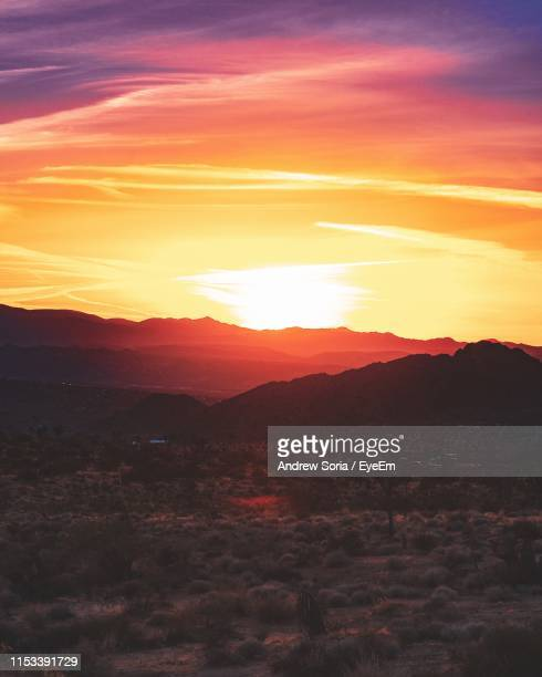 Scenic View Of Landscape Against Romantic Sky At Sunset