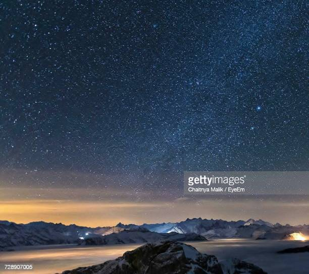 scenic view of landscape against sky at night - snow moon stock pictures, royalty-free photos & images