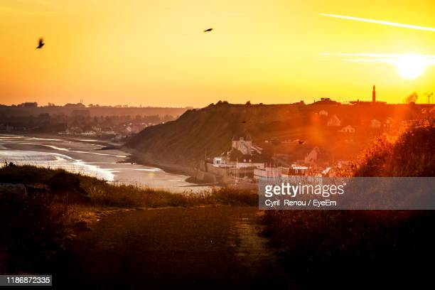 scenic view of landscape against sky during sunset - arromanches stock pictures, royalty-free photos & images